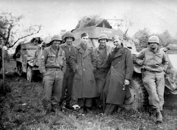 Jim Keeffe with fellow soldiers in front of M3 half-tracks